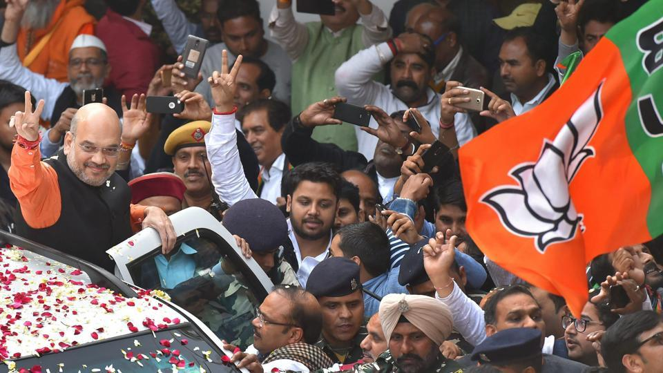 BJP president Amit Shah flashes victory sign as he is welcomed on his arrival at the party headquarters in New Delhi on December 18.