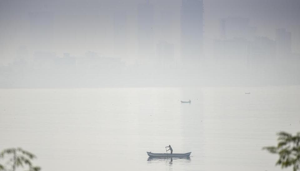Mumbai, India - Dec. 17, 2017: Fishermen fishing in arabian sea as Mumbai Skyline is engulfed by smog at Bnadra in Mumbai,India, on Sunday, December 17, 2017. (Photo by Kunal Patil/ Hindustan Times)