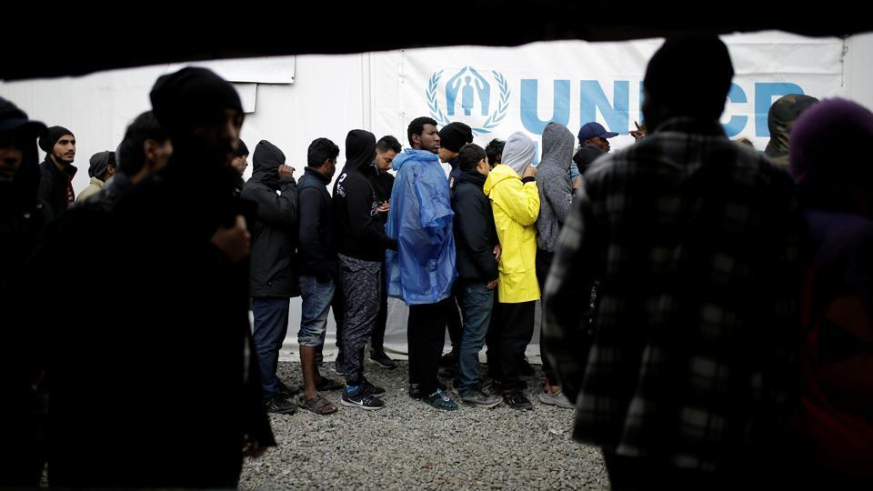 Refugees and migrants line up to receive their lunch provided by the Greek authorities, at a makeshift camp next to the Moria camp on the island of Lesbos, Greece, November 30, 2017.