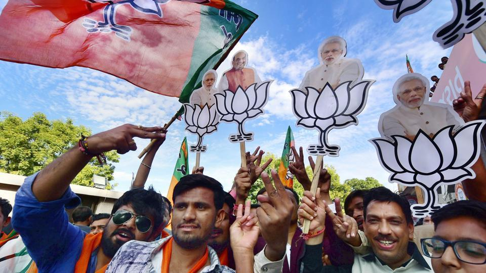 BJP workers celebrate their victory in the assembly elections, at the party office 'Kamlam' in Gandhinagar on Monday.