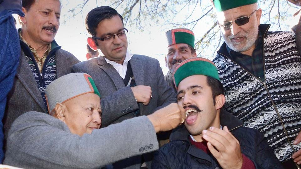 CM Virbhadra Singh celebrates his son Vikramaditya's success as he wins his first assembly election from Shimla rural, at their residence, in Shimla on Monday. BJP won with 44 seats. (PTI)