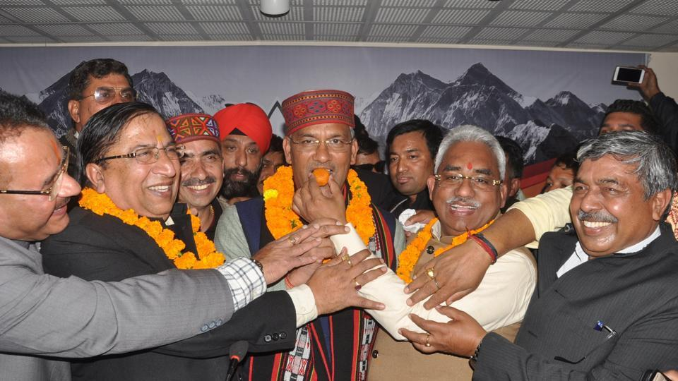 BJP leaders offer sweets to chief minister TS Rawat after BJP's win in Himanchal Pradesh and Gujarat.