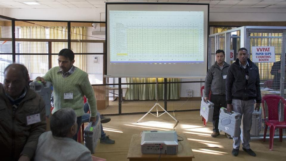 Live results are projected on a screen as election officials hold electronic voting machines at a poll counting center. Narinder Bragta, of the BJP, is the likely winner in Jubbal-Kotkhai constituency, where the brutal rape and murder of a Class 10 girl ignited protests over law and order issue against the Virbhadra Singh government. (Ashwini Bhatia / AP)