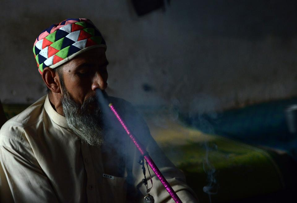 This picture taken on October 25, 2017 shows a Pakistani man smoking hashish in a chillum pipe near a shrine in Peshawar.