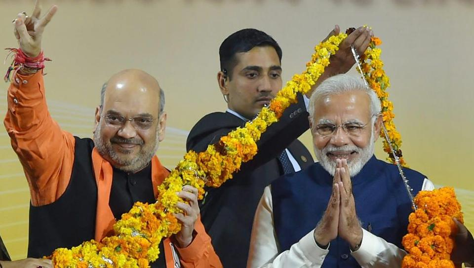 BJP president Amit Shah and Prime Minister Narendra Modi greet supporters after the party's win in Gujarat and Himachal Pradesh assembly elections, at the party headquarters in New Delhi on Monday.
