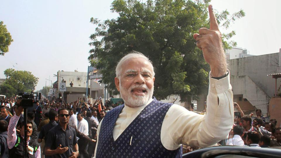 Prime Minister Narendra Modi shows his finger marked with indelible ink, as he leaves after casting his vote, during the second phase of state Assembly elections in Ahmedabad