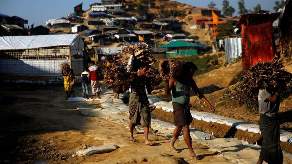Rohingya refugee men carry wood at the Balukhali refugee camp near Cox's Bazar, Bangladesh, on December 17, 2017.