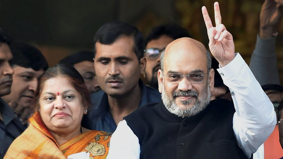 BJP national president Amit Shah with his wife flashes victory sign after casting votes during the second phase of assembly elctions, at Naranpura in Ahmedabad.