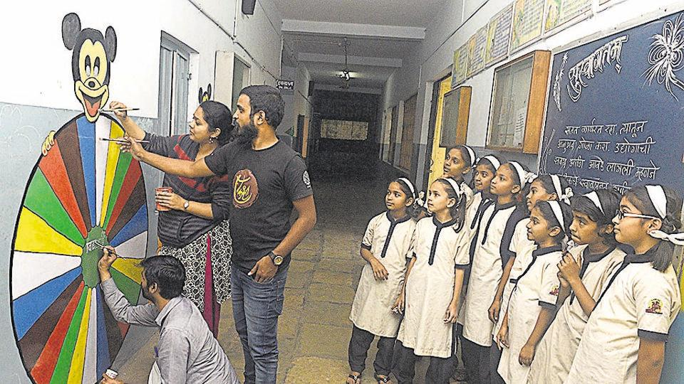 Ashish Patil (sitting), Sushma Kamble (standing) and Sachin Tonde give finishing touches to a graffiti as students of Vidya Niketan school watch them paint their school walls.