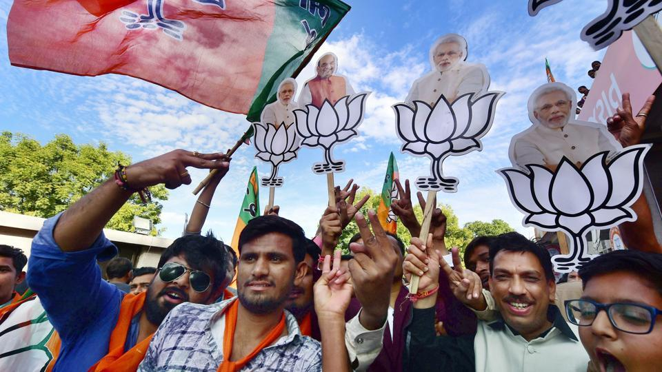 BJP workers celebrate their victory in the assembly elections near the party office 'Kamlam' in Gandhinagar on Monday.