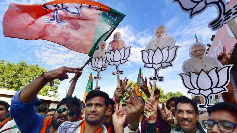 BJP workers celebrate their victory in the Assembly elections, at the party office Gandhinagar, December 19