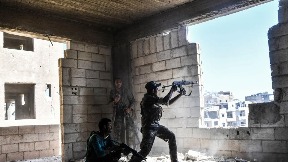 Members of the Syrian Democratic Forces fire their arms during a battle against Islamic State (IS) group jihadists to retake the central hospital of Raqa on the western frontline of the city on September 28, 2017 .