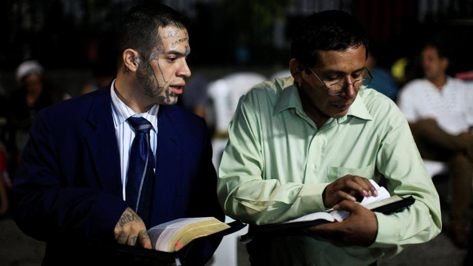"Julio Marroquin, (L), member of the Huellas de Esperanza ministry, participates in a religious service at the Eben-Ezer church in the gang-ridden Dina neighbourhood of San Salvador. Returning to civil society is arduous in the midst of the government's militarized battle against the ""maras,"" which has led to claims of rights abuses and, according to police, an average daily tally of 16 dead. (Jose Cabezas / REUTERS)"