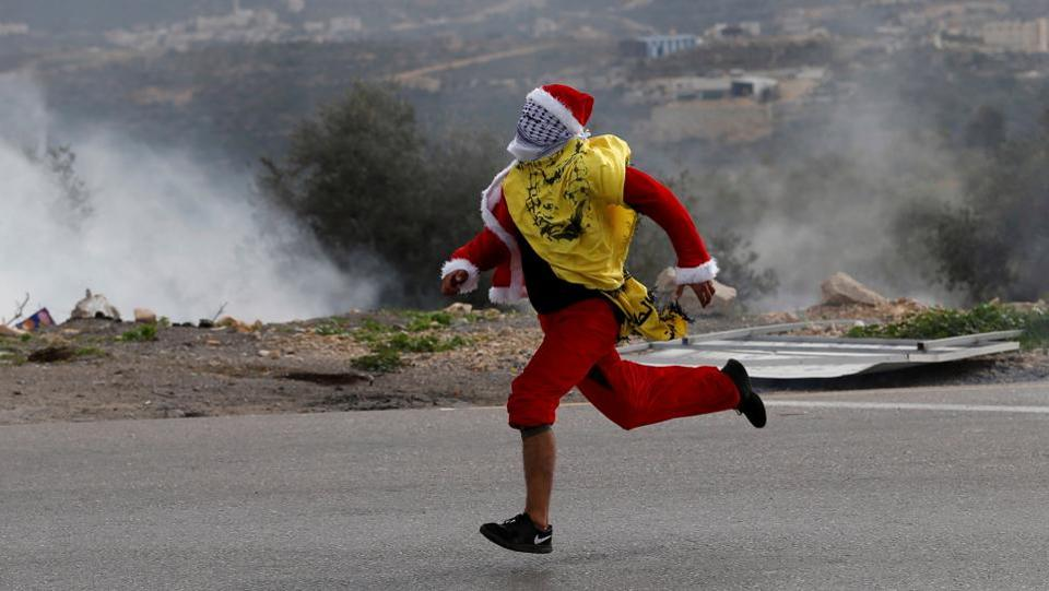 Santa Claus makes a getaway during clashes with Israeli troops at a protest against US President Donald Trump's decision to recognize Jerusalem as the capital of Israel, near the West Bank city of Ramallah. (Mohamad TorokmanREUTERS)