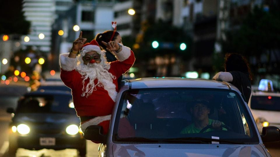 "Tired of all that exercise, Santa chose to hitch a ride instead, while participating in the ""Santa en las calles"" or ""Santa in the Streets"" event to spread Christmas joy among the needy in Caracas, Venezuela. (Federico Parra / AFP)"