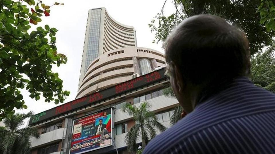 A man looks at a screen across a road displaying the Sensex on the facade of the Bombay Stock Exchange building in Mumbai.