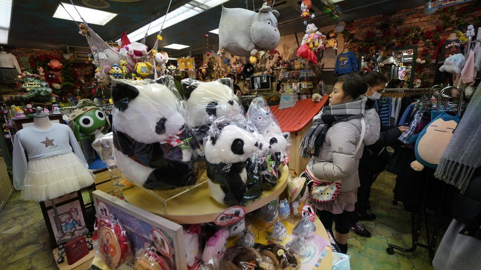 "Customers browse through panda themed goods at a souvenir shop at Ameyoko shopping district near Ueno Zoo. ""For me, the panda is the king of the zoo,"" said Takamichi Masui, 50, who queued nearly three hours to be the first person to see Xiang Xiang. December 23 will be the first public holiday when large crowds are expected to turn up to meet the cub. (Shizuo Kambayashi / AP)"
