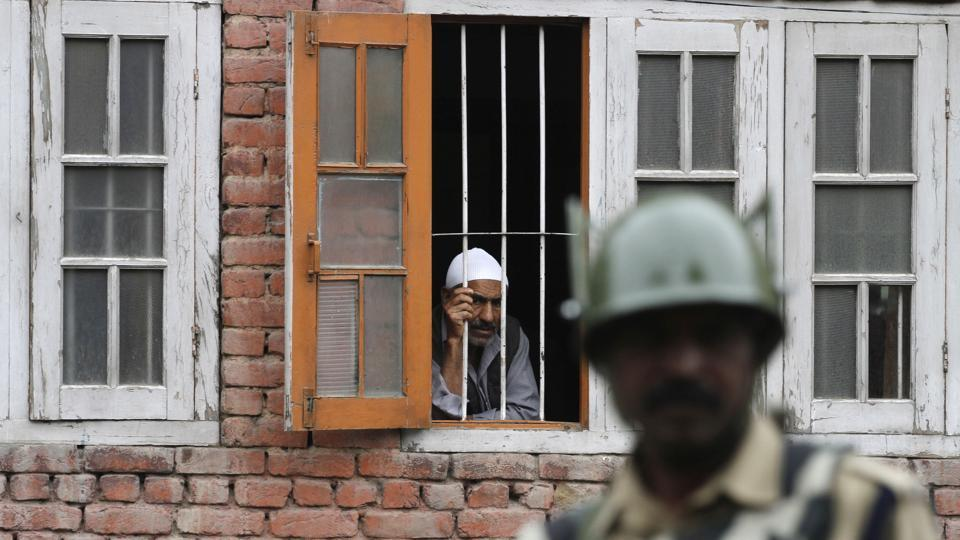 A Kashmiri man looks out from a window as a paramilitary soldier stands guard during a curfew in Srinagar after Wani's death. (Waseem Andrabi / HT Photo)