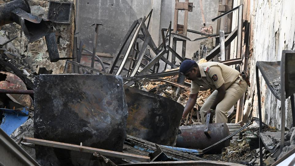 A police officer inspects the site at Sakinaka in Mumbai on Monday.