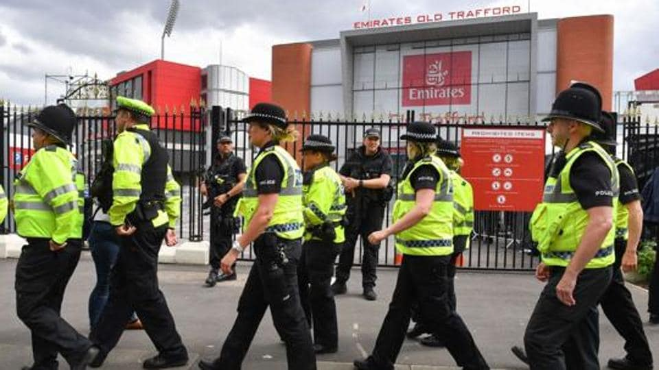 Armed police officers patrol outside the Old Trafford Cricket Ground ahead of the One Love Manchester tribute concert in Manchester on June 4, 2017.