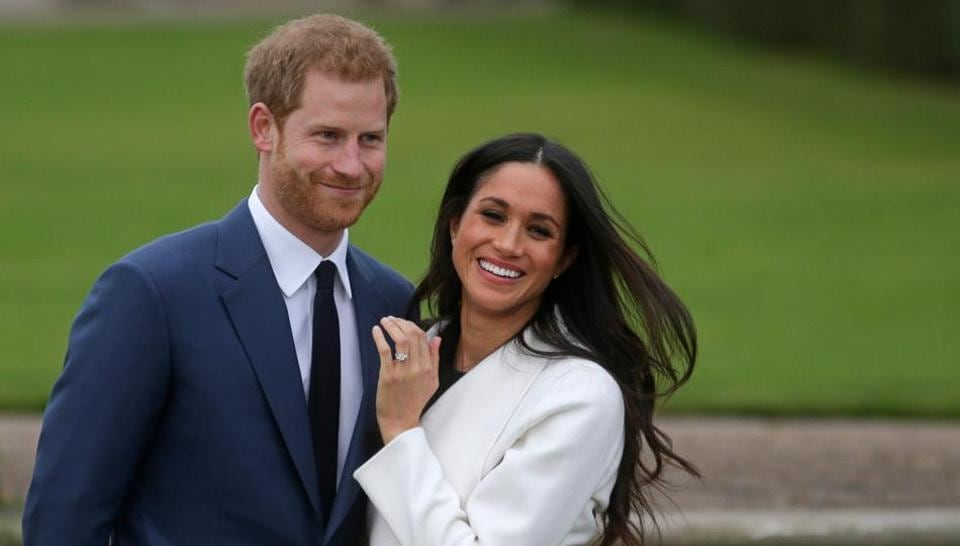 Britain's Prince Harry with his fiancée Meghan Markle as she shows off her engagement ring whilst they pose for a photograph in the Sunken Garden at Kensington Palace in west London, following the announcement of their engagement