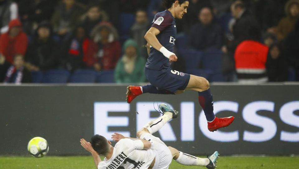 Paris Saint-Germain's (PSG's) Edinson Cavani (top) jumps over Caen's Frederic Guilbert during the French Ligue 1 football match at the Parc des Princes stadium in Paris on Wednesday.