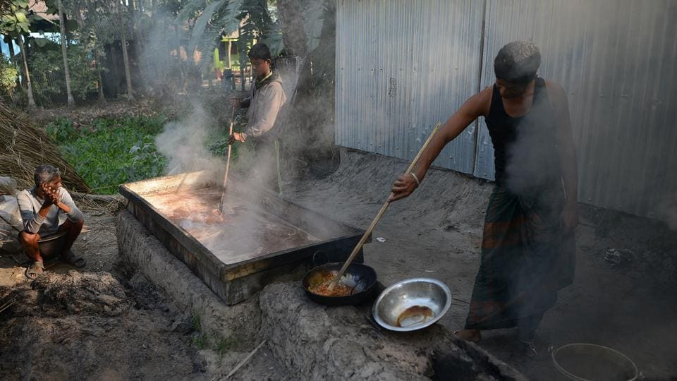 Rahim (L) looks on as his son Alamgir Sheikh (R), 21, boils cane sugar. After collecting the sap from the trees the process includes boiling, filtering and extensive stirring to make a thick paste that is cooled down to form jaggery. Also known as Gur, its production uses sap from four kinds of palm: palmyra, date, coconut and sago. (Diptendu Dutta / AFP)