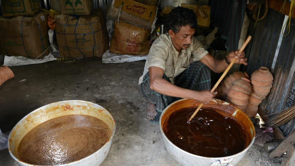 Rahim  filters the boiled sap of the date palm tree. The jaggery made by these workers has found a market among locals and in various parts of North Bengal. When consumed in small quantities, jaggery is considered to have widespread health benefits, as is even gluten free. (Diptendu Dutta / AFP)