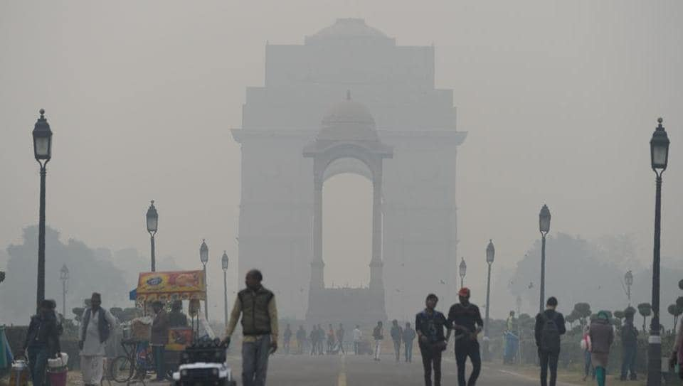 Residents walk amid heavy smog at India Gate in New Delhi on December 20, 2017.