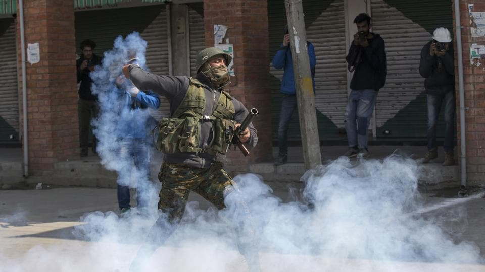 An Indian police man throws back an exploded tear gas shell at Kashmiri protesters during a protest in Srinagar.