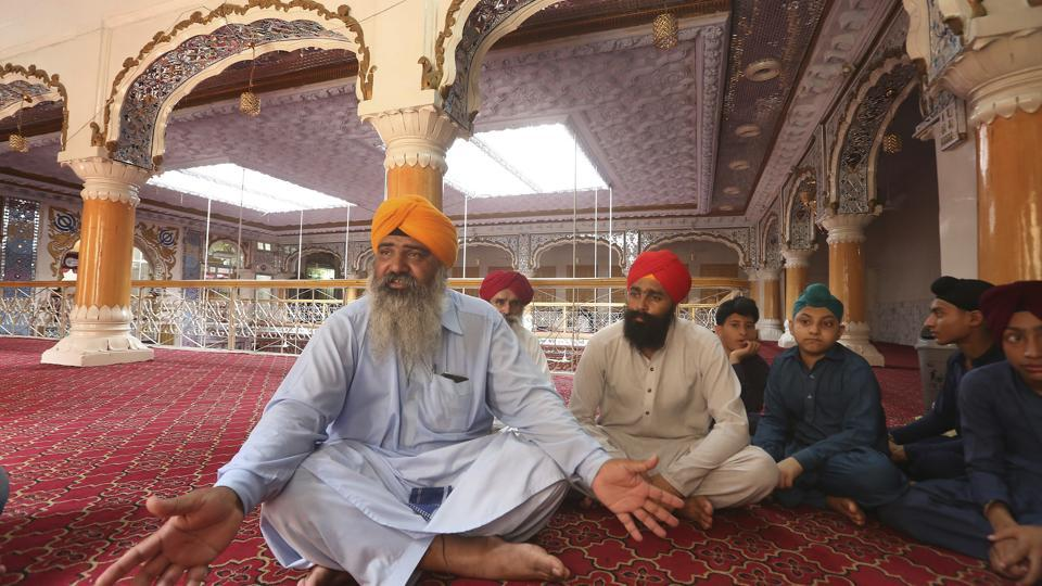 In this Tuesday, Aug. 8, 2017 photo, Pakistani Sikh Radesh Singh, left, talks at a temple in Peshawar, Pakistan.