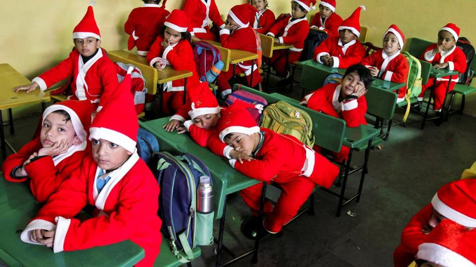 Children dressed in Santa Claus costumes sit inside a classroom before participating in Christmas celebrations at a school in Chandigarh on Wednesday. (Ajay Verma / REUTERS)