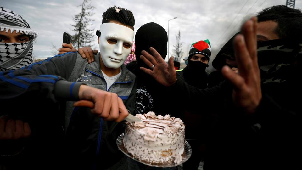 Palestinian demonstrators cut a birthday party during a protest against US President Donald Trump's decision to recognize Jerusalem as Israel's capital, near the Jewish settlement of Beit El, near the West Bank city of Ramallah December 18, 2017. (Mohamad Torokman / REUTERS)