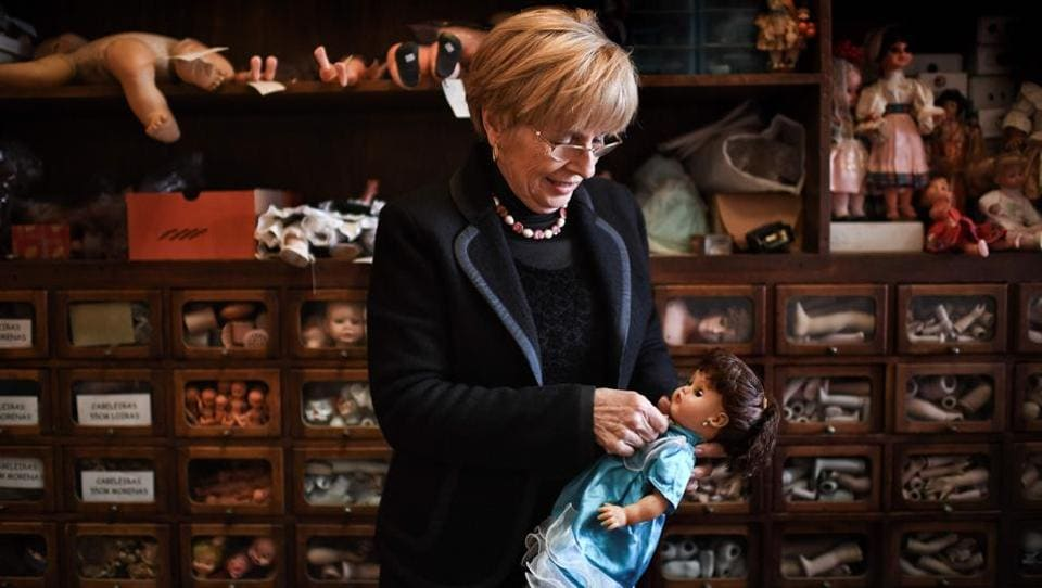 "Manuela Cutileiro dresses up a doll. ""They say we are among the last in the world to do this work,"" the former school teacher says shrugging off accolades. ""We do our work in our little corner, without worrying about records or statistics."" (Patricia De Melo Moreira / AFP)"