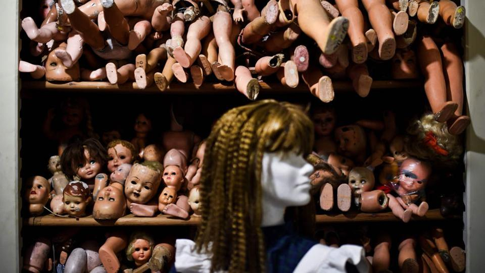 A mannequin is displayed in front of shelves of doll parts. Over time, the aromatic and medicinal herbs gave way to shelves of dolls, which today fill a window display at the entrance to the hospital, with a museum dedicated to them on the first floor. (Patricia De Melo Moreira / AFP)