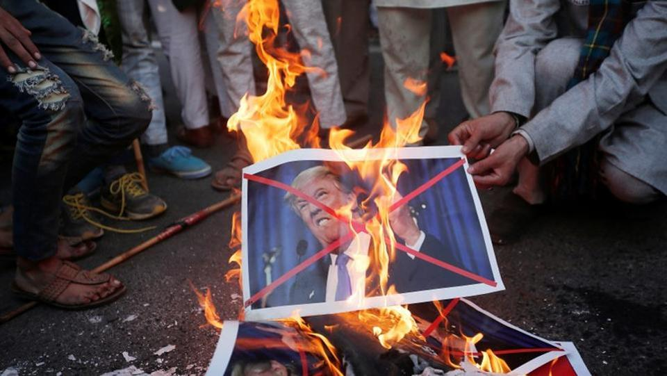 Protestors burn posters of U.S. President Donald Trump organised by various religious organisations against the U.S. decision to recognise Jerusalem as the capital of Israel on Sunday. (Adnan Abidi  /  REUTERS)