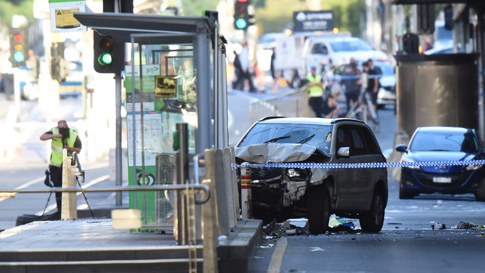 A white SUV (C) sits in the middle of the road as police and emergency personnel work at the scene of where a car ran over pedestrians in Flinders Street in Melbourne on December 21, 2017. The car ploughed into a crowd in Australia's second-largest city on December 21 in what police said was a
