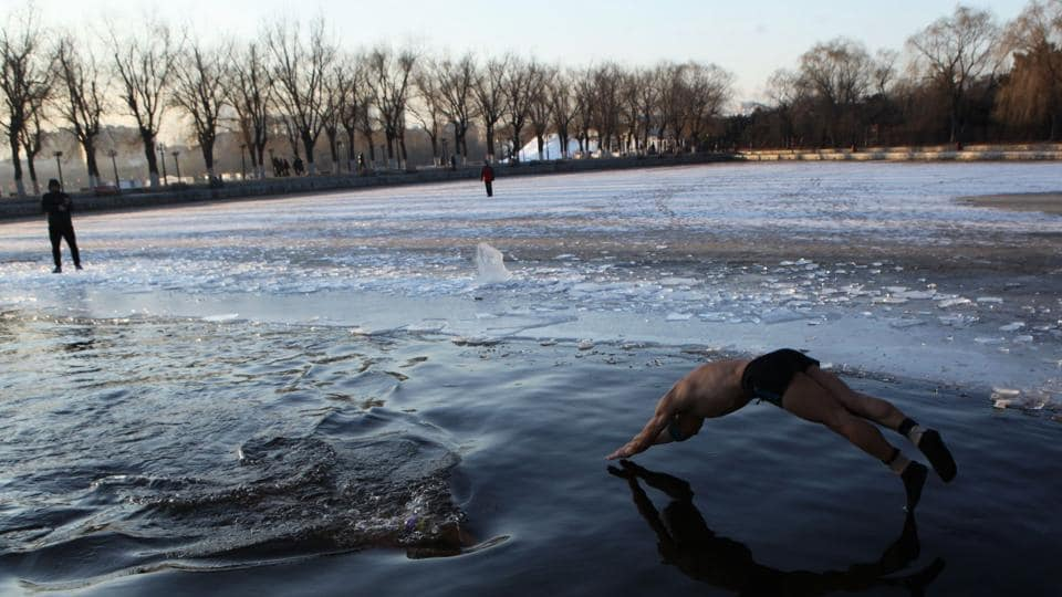 A ice swimmer dives into a partly frozen lake in Shenyang in China's northeastern Liaoning province on December 18, 2017. Winter swimming is believed to improve blood circulation and benefit health. (AFP)