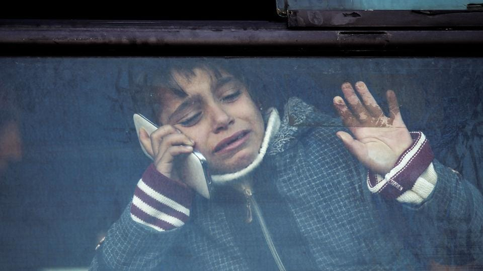 A child holding a phone to her ear bids farewell through the window of a bus in Khan Younis in the southern Gaza strip on December 16, 2017 prior to departure for the Rafah border crossing with Egypt. (Said Khatib / AFP)