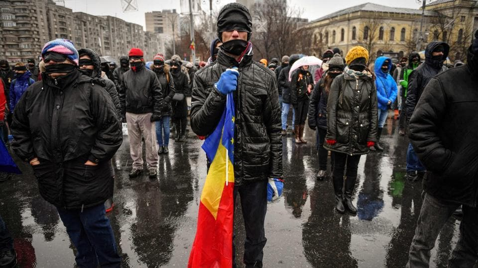 A man holds an EU and a Romanian flag as people, with their eyes and mouths covered with black cloth, take part in a silent flash mob outside the government's headquarters to denounce the left-wing government for backtracking on efforts to fight corruption on December 17, 2017 in Bucharest. More than 10,000 people braved biting cold to stage protests across Romania. (Daniel Mihailescu / AFP)