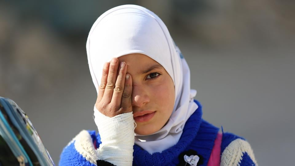 A girl covers one eye with her hand in the rebel-held town of Douma in Syria's besieged eastern Ghouta region on December 18, 2017, as part of a campaign in solidarity with a baby boy, Karim Abdallah, who lost an eye, as well as his mother, in government shelling on the nearby town of Hammouria. (#SolidarityWithKarim campaign / AFP)