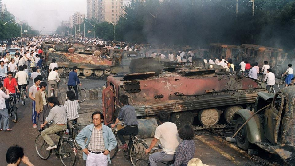 This file photo taken on June 4, 1989 shows Beijing residents gathering around the smoking remains of over 20 armoured personnel carriers burnt by demonstrators during clashes with soldiers near Tiananmen Square.
