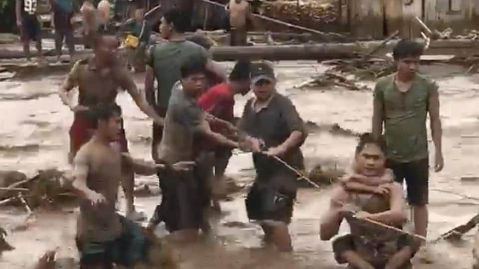 In this video grab, villagers attempt to cross flood waters in Lanao del Norte, Zamboanga Pennisula, southern Philippines in December 22.