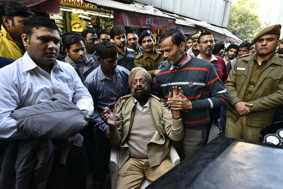 A shopowner reacts as MCD officials seal shops at the Defence Colony Market .