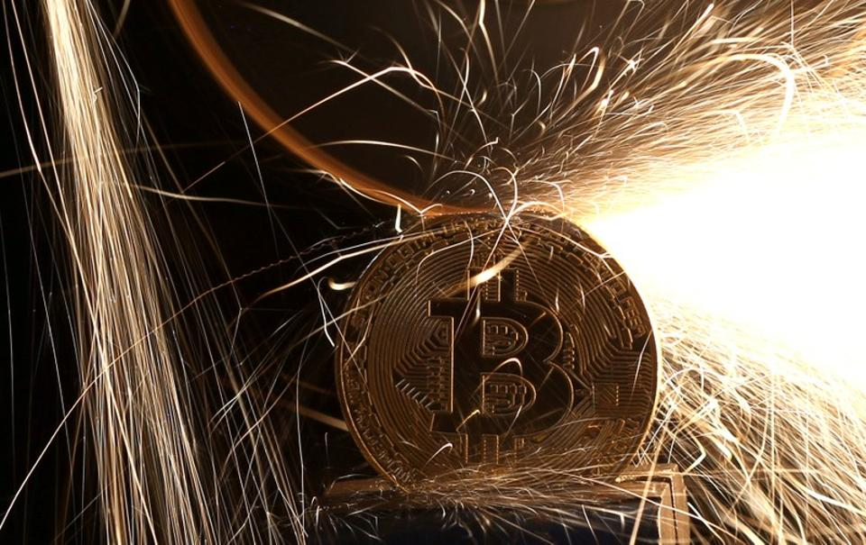 Sparks glow from broken Bitcoin (virtual currency) coins in this illustration picture.