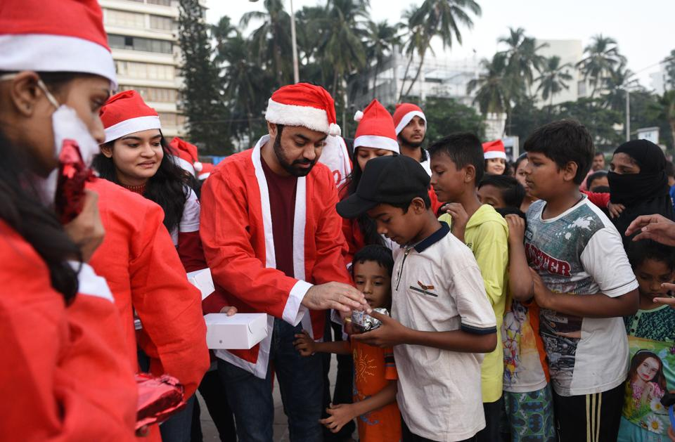 Students distribute gifts to slum kids at Carter Road  on Sunday.