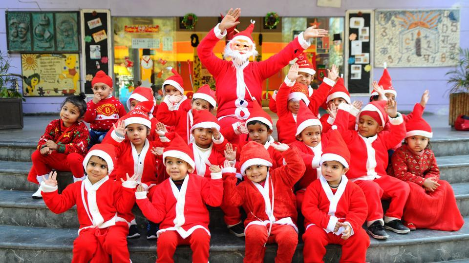 Dressed as Santa Claus, school kids pose for a photograph as they celebrate Christmas at Gian Jyoti Global School, in Mohali on Friday. (Anil Dayal/HT)