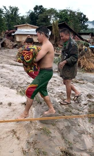 A man carries the body of flood victim in Lanao Del Norte, Philippines, in this December 22, 2017 photo obtained from social media. Courtesy Aclimah Cabugatan Disumala.