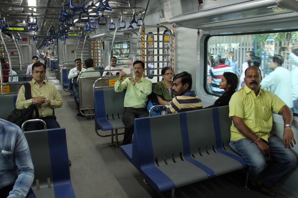 Commuters board the air-conditioned local train at Borivli station in Mumbai on Monday.