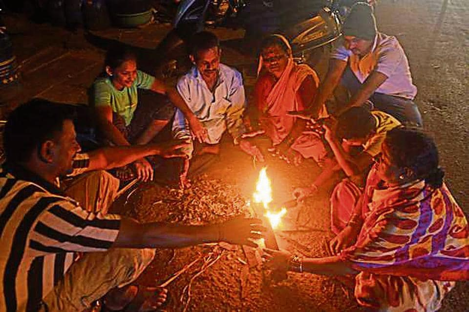 People sit around a campfire to keep themselves warm on a winter evening on Monday.